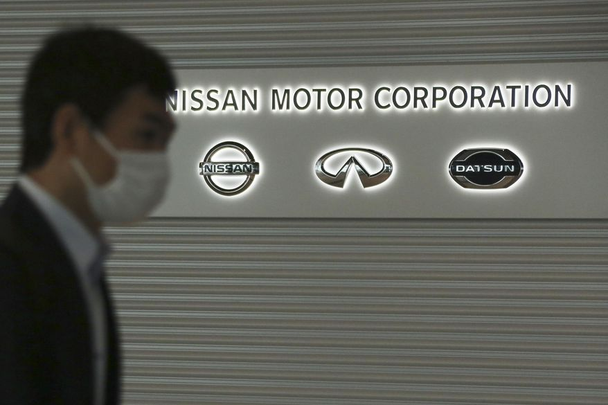 A man walks past the corporate logos at the global headquarters of Nissan Motor Co., Ltd. in Yokohama near Tokyo, Thursday, May 21, 2020. Nissan Chief Executive Makoto Uchida told shareholders Monday, June 29, 2020 he is giving up half his pay as the Japanese automaker sank into the red amid plunging sales and plant closures in Spain and Indonesia. (AP Photo/Koji Sasahara)