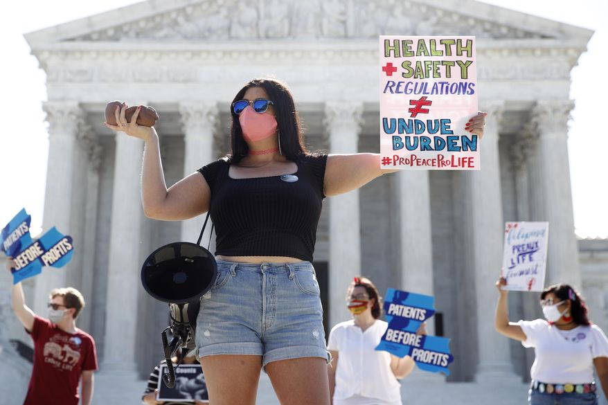 Terrisa Bukovinac, founder of Pro-Life San Francisco, holds a model of a fetus as she and other anti-abortion protesters wait outside the Supreme Court for a decision, Monday, June 29, 2020. The Supreme Court has struck down a Louisiana law regulating abortion clinics, reasserting a commitment to abortion rights over fierce opposition from dissenting conservative justices in the first big abortion case of the Trump era.  (AP Photo/Patrick Semansky) **FILE**