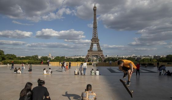 In this Monday, May 25, 2020, file photo, people stroll at Trocadero square near the Eiffel Tower in Paris. European Union envoys are close to finalizing a list of countries whose citizens will be allowed back into Europe once it begins lifting coronavirus-linked restrictions. The United States appears almost certain not to make the list, as new infections surge and given that President Donald Trump has imposed a ban on European travelers. (AP Photo/Michel Euler, File)