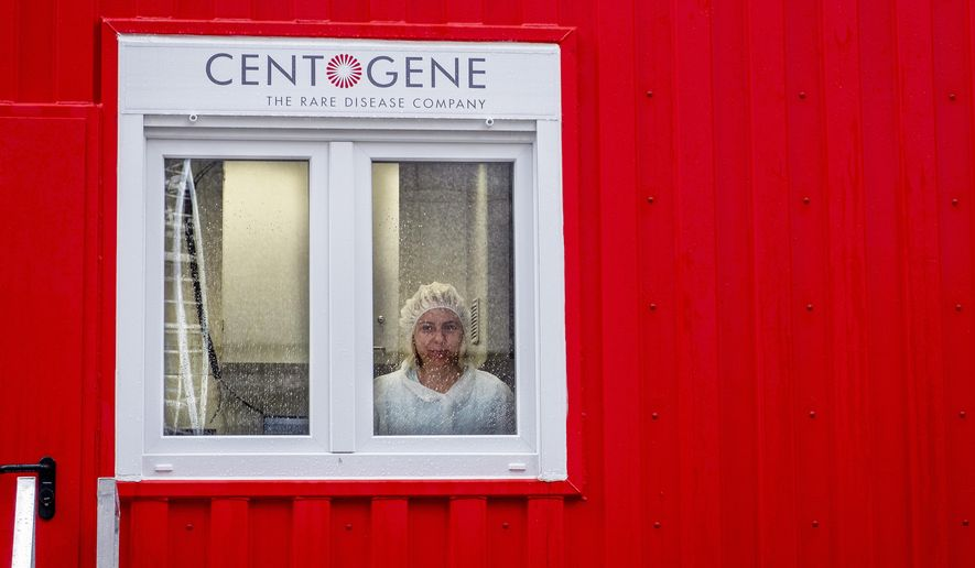 """An employee of Centogene looks out of a laboratory container at the airport in Frankfurt, Germany, Monday, June 29, 2020. In the future, people will be able to be tested for the corona virus within a few hours at Germany's first """"Airport Corona Test"""" centre. (AP Photo/Michael Probst)"""