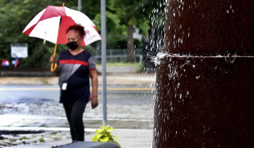 Water drops from a fountain as a woman wearing a mask out of concern for coronavirus walks in the rain, Monday, June 29, 2020, in Lowell, Mass. (AP Photo/Elise Amendola)