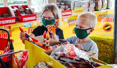 Children pick out fireworks in Omaha, Nebraska, ahead of the Fourth of July. With dozens of cities canceling Fourth of July fireworks shows, celebrants are turning to at-home pyrotechnics. (ASSOCIATED PRESS)