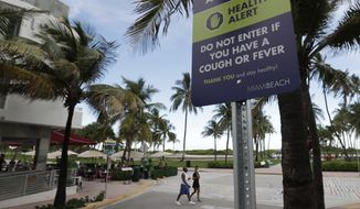 In this June 22, 2020, file photo, a couple walks past a sign asking people not to visit Miami Beach, Florida's famed South Beach, if they have a cough or fever. An Associated Press analysis of coronavirus case data shows the virus has moved, and is spreading quickly, into Republican areas, a new path with broad potential political ramifications. (AP Photo/Wilfredo Lee, File)