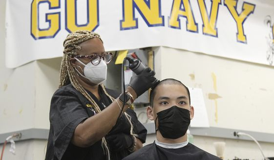 Kenneth Nguyen, 18, from Portland, Oregon, gets his hair cut by hairstylist Lisa Rivera as incoming freshman midshipmen, or plebes, arrive at the United States Naval Academy in Annapolis Tuesday, to begin their Plebe Summer of training during a COVID-19 modified Induction Day. (Paul W. Gillespie/The Baltimore Sun via AP)