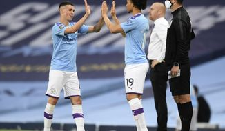 Manchester City's Phil Foden, left, gestures with teammate Leroy Sane as he is substituted during the English Premier League soccer match between Manchester City and Burnley at Etihad Stadium, in Manchester, England, Monday, June 22, 2020. (AP Photo/Michael Regan,Pool)