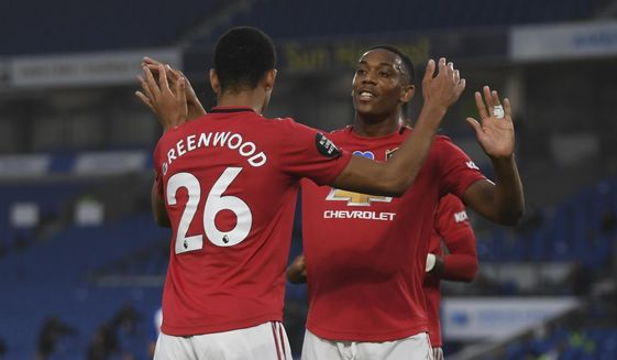 Manchester United players celebrate the opening goal of their team during the English Premier League soccer match between Brighton & Hove Albion and Manchester United at the AMEX Stadium in Brighton, England, Tuesday, June 30, 2020. (Mike Hewitt/Pool via AP)