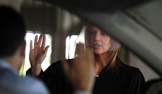 In this June 26, 2020, file photo, U.S. District Judge Laurie Michelson administers the Oath of Citizenship to Ismael Gonzalez during a drive-thru naturalization service in a parking structure at the U.S. Citizenship and Immigration Services headquarters on Detroit's east side. The ceremony is a way to continue working as the federal courthouse is shut down due to the novel coronavirus. The U.S. has resumed swearing in new citizens but the oath ceremonies aren't the same because of COVID-19 and a budget crisis at the citizenship agency threatens to stall them again. (AP Photo/Carlos Osorio)