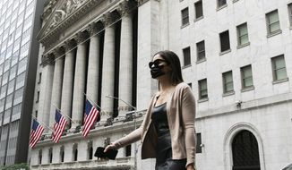 In this file photo, a woman wearing a mask passes the New York Stock Exchange, Tuesday, June 30, 2020, during the coronavirus pandemic. The Congressional Budget Office on July 2, 2020, said it expects a V-shaped economic recovery as the United States rebounds from the coronavirus-related recession. (AP Photo/Mark Lennihan)