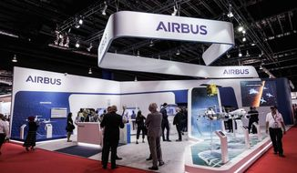 FILE - In this Tuesday, Feb. 11, 2020 file photo, visitors are seen at the booth of Airbus during the opening trade day of the Singapore Airshow 2020 in Singapore. European aircraft manufacturer Airbus says it plans to shed 15,000 jobs over the next year, with jobs mostly being lost in Europe. Airbus is struggling with the financial hit of the coronavirus pandemic. It said Tuesday, June 30 that it doesn't expect air traffic to recover to pre-COVID levels before 2023 and potentially as late as 2025. (AP Photo/Danial Hakim, file)