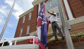 FILE - In this Monday, June 29, 2020, file photo, City of Tupelo Community Outreach Coordinator Marcus Gary takes down the Mississippi state flag that flew over the City Hall of Tupelo one last time Monday, June 29, 2020. Mississippi is retiring the last state flag in the U.S. that includes the Confederate battle emblem. (Thomas Wells/The Northeast Mississippi Daily Journal via AP, File)