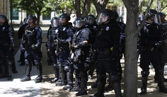 Officers in riot gear guard the police department Saturday, June 27, 2020, in Aurora, Colo., during a rally and march over the death of Elijah McClain. McClain was a 23-year-old Black man put into a chokehold by police last year. He suffered cardiac arrest on the way to the hospital and was later declared brain dead and removed from life support. (AP Photo/David Zalubowski) **FILE**