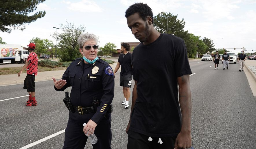"""FILE - In this June 2, 2020, file photo, interim Aurora Police Chief Vanessa Wilson and Jay B. confer as protesters march north on South Chambers Road during a peaceful protest against police brutality following the death of George Floyd in Aurora, Colo. Multiple suburban Denver police officers have been placed on paid administrative leave amid an investigation into photos of them related to the case of a Black man who died last summer after he was stopped and restrained, police said Monday, June 29. Wilson said in a statement that the suspended officers were """"depicted in photographs near the site where Elijah McClain died."""" But her statement did not provide more details about what the images show. (Philip B. Poston/The Aurora Sentinel via AP, File)"""