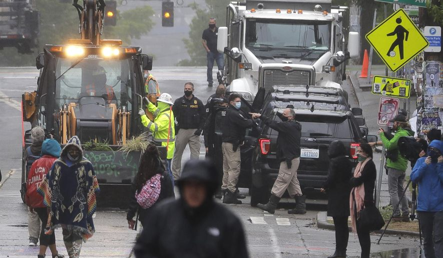 Seattle Police, at right, look on as Department of Transportation workers remove barricades at the intersection of 10th Ave. and Pine St., Tuesday, June 30, 2020, at the CHOP (Capitol Hill Occupied Protest) zone in Seattle. Protesters quickly moved couches, trash cans and other materials in to replace the cleared barricades. The area has been occupied by protesters since Seattle Police pulled back from their East Precinct building following violent clashes with demonstrators earlier in the month. (AP Photo/Ted S. Warren)