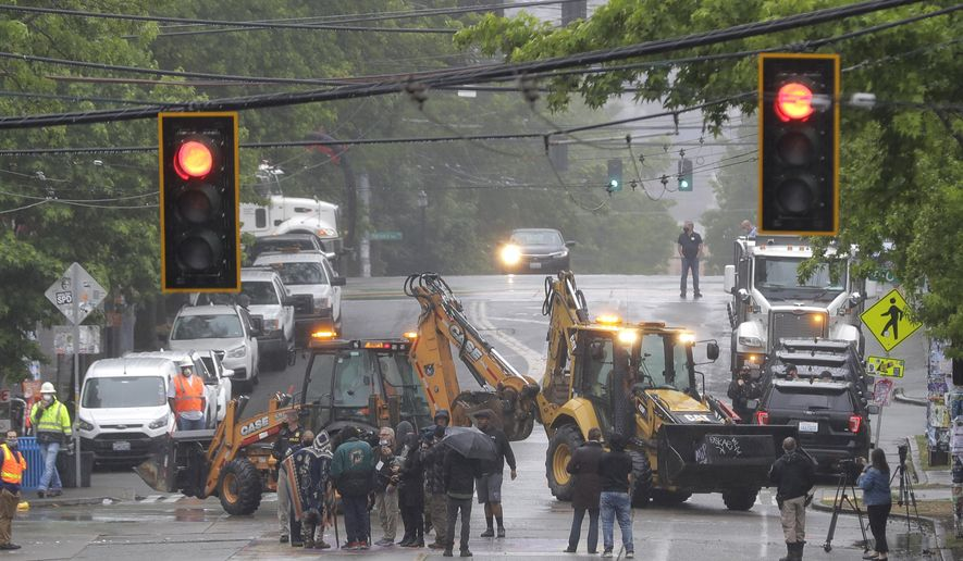 Seattle Department of Transportation workers remove barricades at the intersection of 10th Ave. and Pine St., Tuesday, June 30, 2020 at the CHOP (Capitol Hill Occupied Protest) zone in Seattle. Protesters quickly moved couches, trash cans and other materials in to replace the cleared barricades. The area has been occupied by protesters since Seattle Police pulled back from their East Precinct building following violent clashes with demonstrators earlier in the month. (AP Photo/Ted S. Warren)