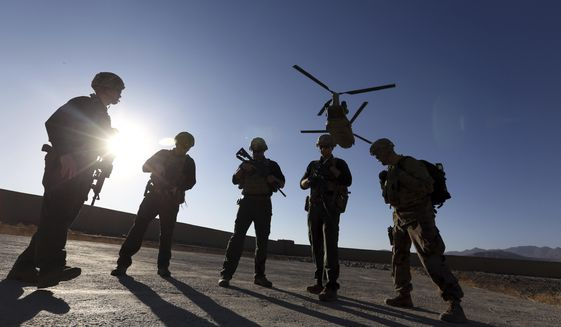 In this Nov. 30, 2017, file photo, American soldiers wait on the tarmac in Logar province, Afghanistan. Top officials in the White House were aware in early 2019 of classified intelligence indicating Russia was secretly offering bounties to the Taliban for the deaths of Americans, a full year earlier than has been previously reported. (AP Photo/Rahmat Gul, File)