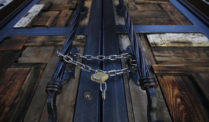 Bottled Blonde, one of the many restaurant bars closed for the next 30 days due to the surge in coronavirus cases, is padlocked shut Tuesday, June 30, 2020, in Scottsdale, Ariz. (AP Photo/Ross D. Franklin)
