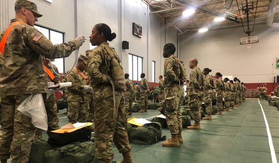 In this image provided by the U.S. Army, recent Army basic combat training graduates have their temperatures taken as they arrive at Fort Lee, Va, on March 31, 2020, after being transported using sterilized buses from Fort Jackson, S.C. COVID-19 has had a dramatic impact on military recruiting, shuttering enlistment stations around the country and forcing thousands of recruiters to woo potential soldiers online. Recruiters have had to abandon their normal visits to high schools and malls, and instead rely almost exclusively on social media to reach young people. (U.S. Army via AP) **FILE**