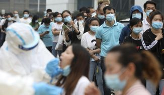 In this Friday, May 15, 2020 file photo, people line up for coronavirus testing at a large factory in Wuhan in central China's Hubei province. In June 2020, China reported using batch testing as part of a recent campaign to test all 11 million residents of Wuhan, the city where the virus first emerged late in late 2019. (Chinatopix Via AP)