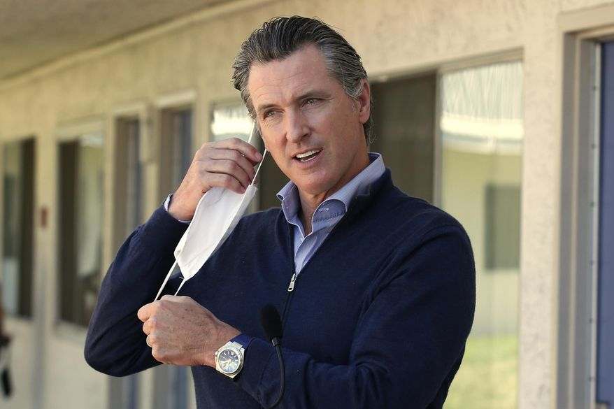 "Gov. Gavin Newsom removes his face mask before giving an update on the state's initiative to provide housing for homeless Californians to help stem the coronavirus, during a visit to a Motel 6 participating in the program in Pittsburg, Calif., Tuesday, June 30, 2020. Newsom announced that more than 15,000 rooms have been acquired and more than 14,000 people have been given places to stay statewide under the Project Room key program started in April. The governor also said he plans to announce on Wednesday plans to ""toggle back"" the states stay-at-home order. (AP Photo/Rich Pedroncelli, Pool)"
