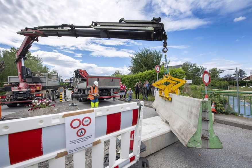 In this  Sunday, June 14, 2020 file photo, a crane removes the concrete blocks that closed customs access, in Thonex near Geneva, Switzerland. The European Union is set to make public on Tuesday, June 30, 2020, a list of countries whose citizens will be allowed to enter 31 European countries, but most Americans are likely to be refused entry for at least another two weeks due to soaring coronavirus infections in the U.S. (Martial Trezzini/Keystone via AP, File)