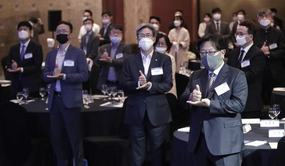 "Participants wearing face masks to help protect against the spread of the new coronavirus gesture as they join the ""Thank You Challenge"" for medical workers fighting the coronavirus during the Yonhap News Symposium on Korean Peace in Seoul, South Korea, Tuesday, June 30, 2020. (AP Photo/Ahn Young-joon)"
