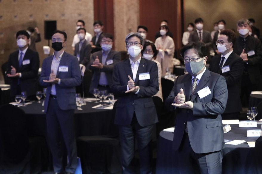 """Participants wearing face masks to help protect against the spread of the new coronavirus gesture as they join the """"Thank You Challenge"""" for medical workers fighting the coronavirus during the Yonhap News Symposium on Korean Peace in Seoul, South Korea, Tuesday, June 30, 2020. (AP Photo/Ahn Young-joon)"""