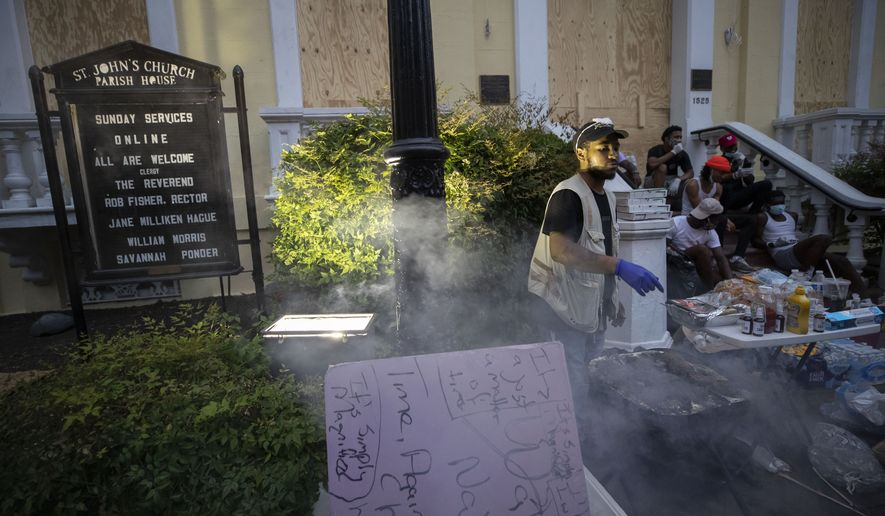 People set up tables and provide free food and drinks on the sidewalk in front of St. John's Church as demonstrators protest Thursday, June 4, 2020, near the White House in Washington, over the death of George Floyd, a black man who was in police custody in Minneapolis. Floyd died after being restrained by Minneapolis police officers. (AP Photo/Alex Brandon)