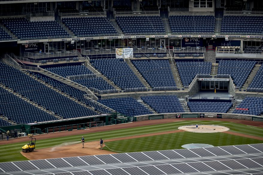 Solar panels on top of a parking garage are visible as workers water the infield at Washington Nationals Stadium, Wednesday, July 1, 2020, in Washington. (AP Photo/Andrew Harnik) ** FILE **