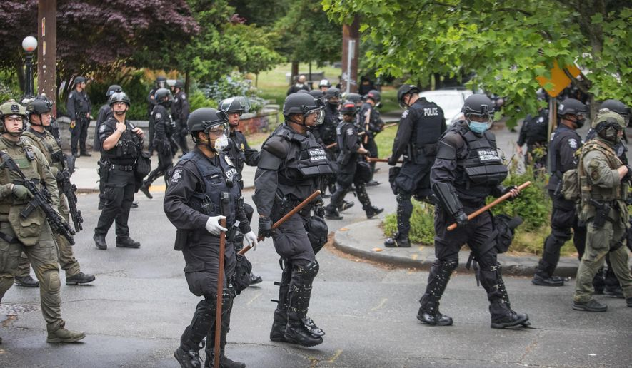 Seattle Police finish their sweep Wednesday, July 1, 2020, on the north end of Cal Anderson Park, sweeping everyone off the grounds.  (Steve Ringman/The Seattle Times via AP)