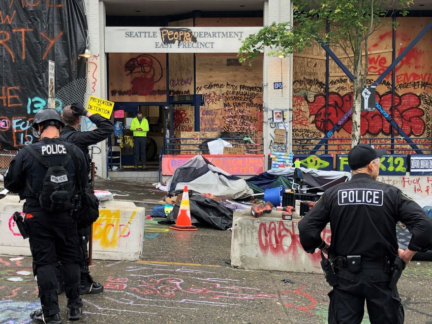 Seattle police enter the East Precinct in Seattle on Wednesday, July 1 2020 after clearing out the CHOP zone.  (Steve Ringman/The Seattle Times via AP)