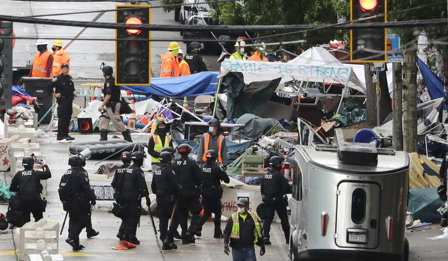 """Police and city workers fill a street occupied hours earlier by an encampment of protesters Wednesday, July 1, 2020, in Seattle, where streets had been blocked off in an area demonstrators had occupied for weeks. Seattle police showed up in force earlier in the day at the """"occupied"""" protest zone, tore down demonstrators' tents and used bicycles to herd the protesters after the mayor ordered the area cleared following two fatal shootings in less than two weeks. The """"Capitol Hill Occupied Protest"""" zone was set up near downtown following the death of George Floyd while in police custody in Minneapolis. (AP Photo/Elaine Thompson)"""