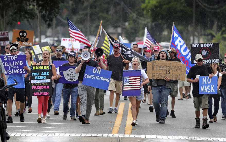 Demonstrators march through downtown Sanford, Fla., Wednesday, July 1, 2020, to protest a Seminole County order requiring people to wear masks in response to the spike in coronavirus cases. Seminole County officials on Monday issued the executive order that made wearing a mask inside a business or when attending public gatherings indoors mandatory. (Joe Burbank/Orlando Sentinel via AP)