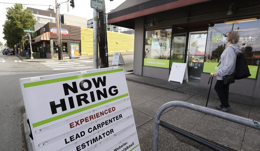 In this June 4, 2020, file photo, a pedestrian wearing a mask walks past a reader board advertising a job opening for a remodeling company, in Seattle. U.S. companies added nearly 2.4 million jobs in June, according to a private survey, a large gain that still leaves the job market far below its pre-pandemic levels. The payroll company ADP said that small businesses reported the largest gain, adding 937,000 jobs. Construction firms and restaurants and hotels also posted big increases in hiring. (AP Photo/Elaine Thompson, File)