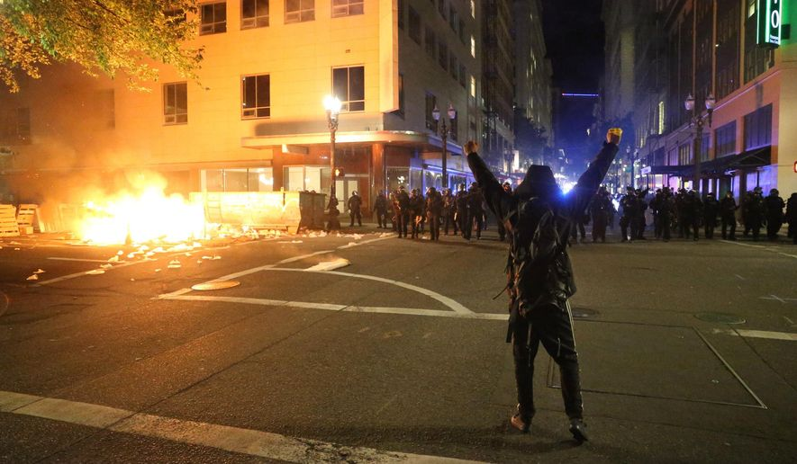 """In this March 29, 2020, file photo, a protester faces police officers in downtown in Portland, Ore. Portland, Oregon, a liberal city with a reputation for full-throated and frequent protests, is reeling from the nightly chaos in its streets and on Wednesday, June 3, 2020, its visibly frustrated police chief appealed to residents to help stop """"those who are holding our city with violence."""" For five consecutive nights, smaller groups of demonstrators have broken off from peaceful and well-organized protests that have attracted thousands and engaged with police into the wee hours. (Dave Killen/The Oregonian via AP, File)"""
