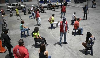 A worker from the Transportation Ministry explains proper mask usage to non-compliant pedestrians on a corner of downtown Caracas, Venezuela, Monday, June 29, 2020, amid efforts to contain the spread of the new coronavirus. (AP Photo/Matias Delacroix)