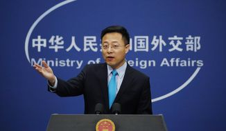 FILE - In this Feb. 24, 2020, file photo, Chinese Foreign Ministry spokesman Zhao Lijian gestures as he speaks during a daily briefing at his ministry in Beijing. China has demanded staff and business information from four U.S. media companies including The Associated Press in what it called a necessary response to similar demands by Washington on Chinese state-controlled news outlets. Lijian announced Wednesday, July 1, 2020, that AP, United Press International, CBS and National Public Radio had seven days to file declarations regarding their staff, financial operations, real estate ownership and other matters. (AP Photo/Andy Wong)