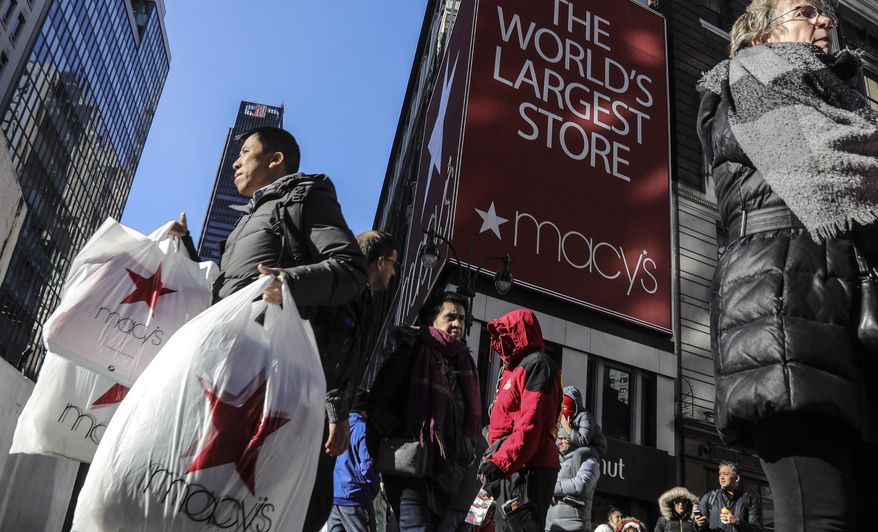 """FILE - In this Nov. 29, 2019, file photo a shopper leaves Macy's department store with bags in both hands during Black Friday shopping in New York. Macy's is refashioning what the Black Friday sales bonanza will look like in a pandemic. The company's CEO Jeff Gennette told analysts Wednesday, July 1, 2020, said that the department store chain will be pivoting its Black Friday business more toward online and will likely be going """"full force"""" with marketing right after Halloween.  (AP Photo/Bebeto Matthews, File)"""