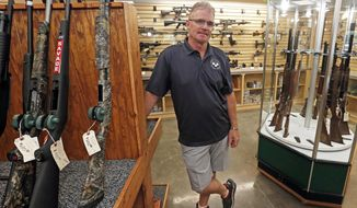 In this Thursday, June. 18, 2020, photo, West Quincy Pawn Shop owner Lionel Hammond poses for a photo in the gun section of the store which Hammond pointed out has a noticeably low stock in West Quincy, Mo. At West Quincy Pawn Shop, Hammond said sales have been off the charts and that he can't keep merchandise on the shelves as buyers are using their governmental stimulus money to buy firearms, jewelry, televisions and other electronics. (Jake Shane/Quincy Herald-Whig via AP) **FILE**