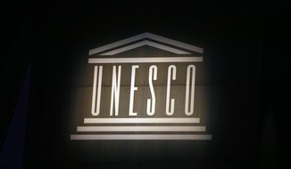 FILE - In this Oct.31 2017 file photo, the logo of the United Nations Educational, Scientific and Cultural Organisation (UNESCO) is seen during the 39th session of the General Conference at the UNESCO headquarters in Paris. The U.N.'s cultural agency UNESCO has warned that its name and logo are being illegally emblazoned on false documents to facilitate illicit trafficking in African cultural property. (AP Photo/Francois Mori, File)