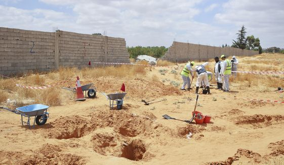 Libyan Ministry of justice employees dig out at a siyte of a suspected mass grave in the town of Tarhouna, Libya, Tuesday, June 23, 2020. The United Nations said that at least eight mass graves have been discovered, mostly in Tarhuna, a key western town that served as a main stronghold for Khalifa's east-based forces in their 14-month campaign to capture the capital, Tripoli. (AP Photo/Hazem Ahmed)