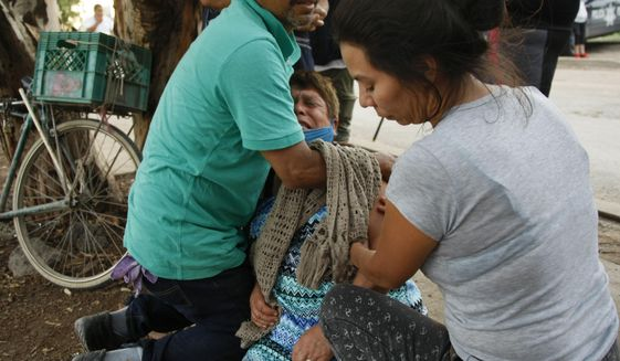 Relatives comfort a woman crying outside an unregistered drug rehabilitation center in Irapuato, Mexico, Wednesday, July 1, 2020, after gunmen burst into the facility and opened fire. According to police at least 24 people were killed in the attack. (AP Photo/Mario Armas)