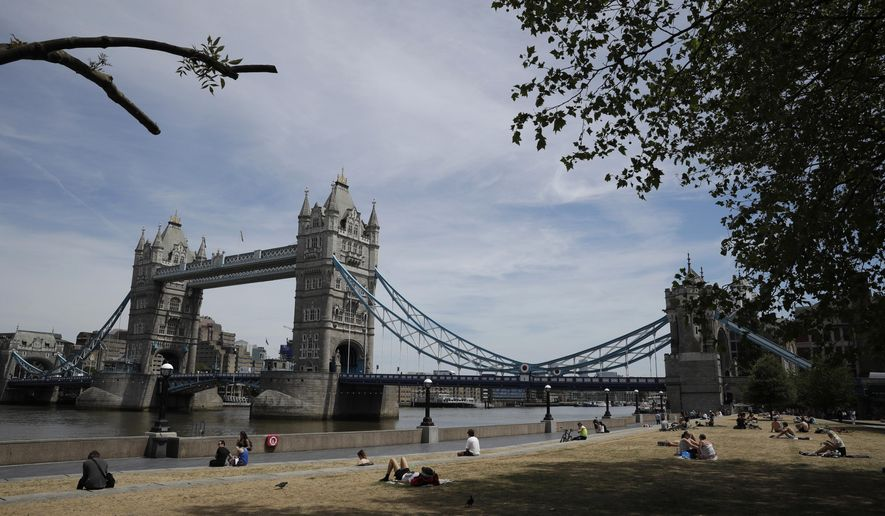 FILE - In this file photo dated Tuesday, June 2, 2020, a few people relax in the sun backdropped by Tower Bridge spanning the River Thames in London.  Some companies linked to hospitality and travel in Britain Wednesday July 1, 2020, have announced thousands of more job cuts as the longer term consequences of the COVID-19 pandemic take hold, choosing to slim down now for survival rather than await future potential government handouts.(AP Photo/Matt Dunham, FILE)