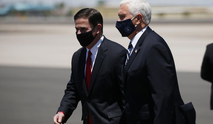 Vice President Mike Pence, right, walks with Arizona Gov. Doug Ducey, left, as the two head to a meeting to discuss the surge in coronavirus cases Wednesday, July 1, 2020, in Phoenix. (AP Photo/Ross D. Franklin)