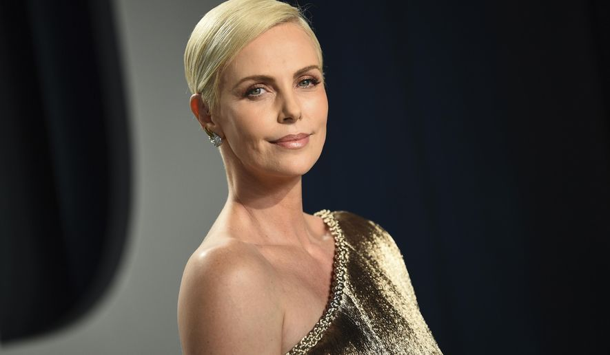 """FILE - This Feb. 9, 2020 file photo shows actress Charlize Theron at the Vanity Fair Oscar Party in Beverly Hills, Calif. Theron stars and produces the Netflix action thriller """"The Old Guard,"""" streaming on July 10. (Photo by Evan Agostini/Invision/AP, File)"""