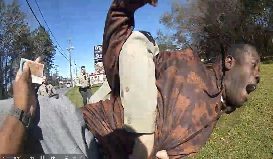 In this still image from body camera video released by the Valdosta police, Antonio Arnelo Smith is slammed face-first to the ground by a Valdosta police sergeant, in Valdosta, Ga., on Feb. 8, 2020. The video shows Smith handing his driver's license to a police officer and answering questions cooperatively before a second officer, Sgt. Billy Wheeler, approaches him from behind, wraps him in a bear hug and slams him face-first to the ground. Smith is crying in pain when he's told there's a warrant for his arrest. Officers are then told the warrant was for someone else. (Valdosta Police via AP)