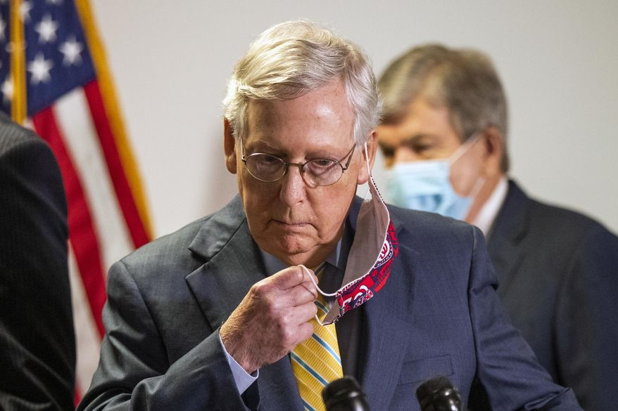 Senate Majority Leader Mitch McConnell, R-Ky., takes off his face mask as he walks toward the podium following a GOP policy meeting on Capitol Hill, Tuesday, June 30, 2020, in Washington. With McConnell is Sen. Roy Blunt, R-Mo. (AP Photo/Manuel Balce Ceneta)