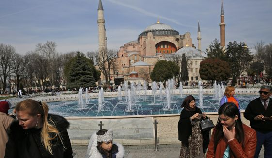 In this Friday, March 24, 2017, file photo, people walk backdropped by the Byzantine-era Hagia Sophia, one of Istanbul's main tourist attractions, in the historic Sultanahmet district of Istanbul. The 6th-century building is now at the center of a heated debate between conservative groups who want it to be reconverted into a mosque and those who believe the World Heritage site should remain a museum. (AP Photo/Lefteris Pitarakis, File)