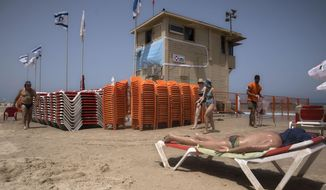 A lifeguard stand is decorated with a large mask to remind people to wear masks as precaution against the new coronavirus at a beach in Tel Aviv, Israel, Sunday, June 21, 2020. (AP Photo/Sebastian Scheiner)