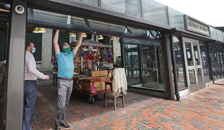 Chris Sherman, second from left, operations manager of Faneuil Hall Marketplace, opens a large window to kiosks as it reopens to the public, Wednesday, July 1, 2020, in Boston. The market, which includes several buildings of retail outlets and restaurants and lined with cobblestone walkways, was closed in March because of the coronavirus pandemic. (AP Photo/Elise Amendola)