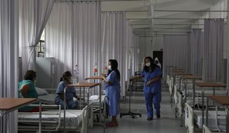 Coronavirus patients in various stages of recovery talk inside the women's ward at a COVID-19 hospital inside Military Camp 1, in Naucalpan, Mexico State, part of the Mexico City metropolitan area, Tuesday, June 23, 2020. The hospital is one of more than 100 converted spaces operated by the military to treat COVID-19 patients, but since it opened in May only about half its beds have been occupied. (AP Photo/Rebecca Blackwell)